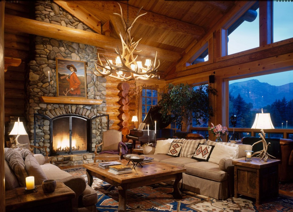 Cozy seating area around a river rock fireplace in a beautiful log home with mountain views.